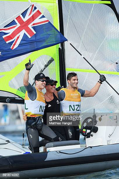Peter Burling of New Zealand and Blair Tuke of New Zealand celebrate with team staff member after winning the gold medal in the Men's 49er class at...