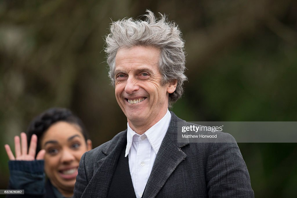 Peter Capaldi, who plays the Doctor, smiles to the camera while the Doctor's companion Pearl Mackie waves during filming for series 10 of BBC show Doctor Who at Cardiff University's Main building on January 26, 2017 in Cardiff, Wales.