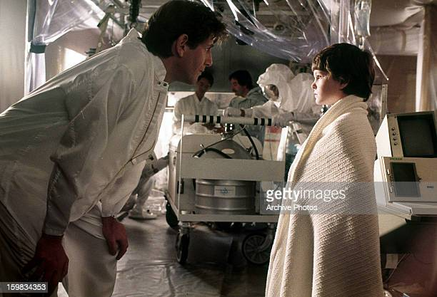 Peter Coyote leaning over to talk to Henry Thomas in a scene from the film 'ET The ExtraTerrestrial' 1982