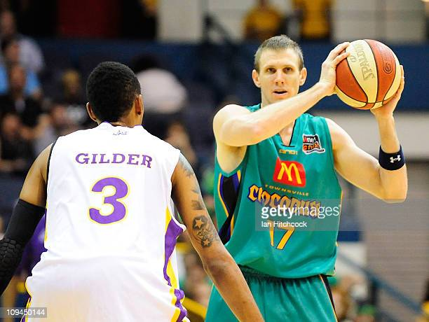 Peter Crawford of the Crocodiles looks to pass the ball past Trey Gilder of the Kings during the round 20 NBL match between the Townsville Crocodiles...