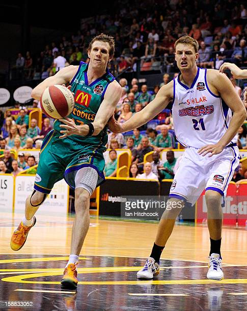 Peter Crawford of the Crocodiles passes the ball past Daniel Johnson of the 36ers during the round 12 NBL match between the Townsville Crocodiles and...