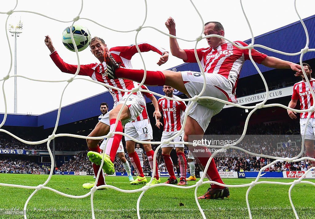 Peter Crouch and Charlie Adam of Stoke City fail to stop the header by Steven Caulker of QPR for the equalising goal during the Barclays Premier League match between Queens Park Rangers and Stoke City at Loftus Road on September 20, 2014 in London, England.