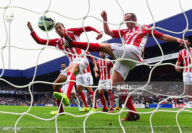 Peter Crouch and Charlie Adam of Stoke City fail to stop the header by Steven Caulker of QPR for the equalising goal during the Barclays Premier...