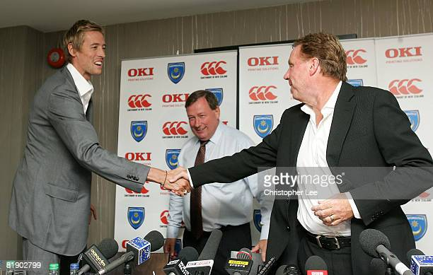 Peter Crouch and manager Harry Redknapp shake hands as they attend the press conference to announce the signing of Peter Crouch to Portsmouth FC at...