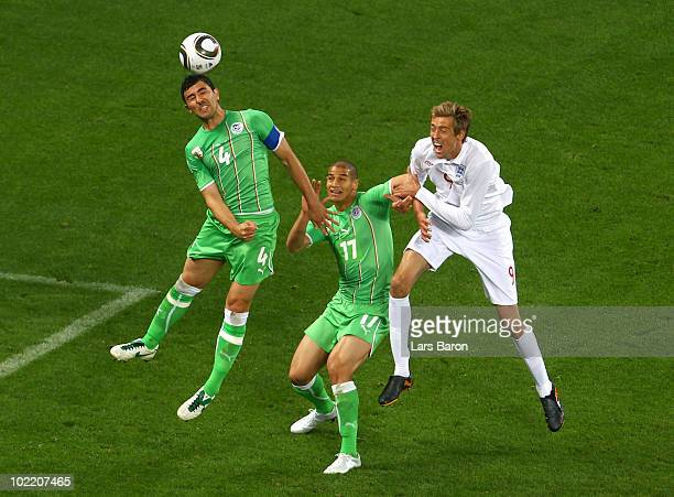 Peter Crouch of England challenges Anther Yahia and Adlane Guedioura of Algeria during the 2010 FIFA World Cup South Africa Group C match between...