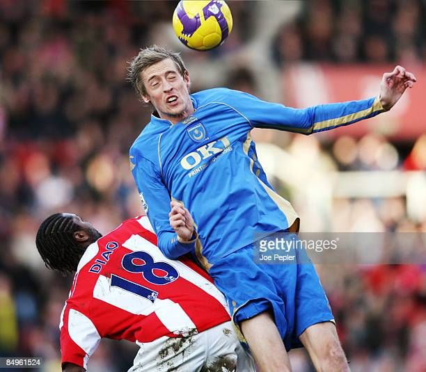 Peter Crouch of Portsmouth competes against Salif Diao of Stoke City during the Barclays Premier League match between Stoke City and Portsmouth at...