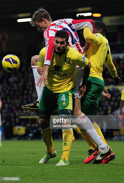Peter Crouch of Stoke City battles with Bradley Johnson of Norwich City during the Barclays Premier League match between Norwich City and Stoke at...