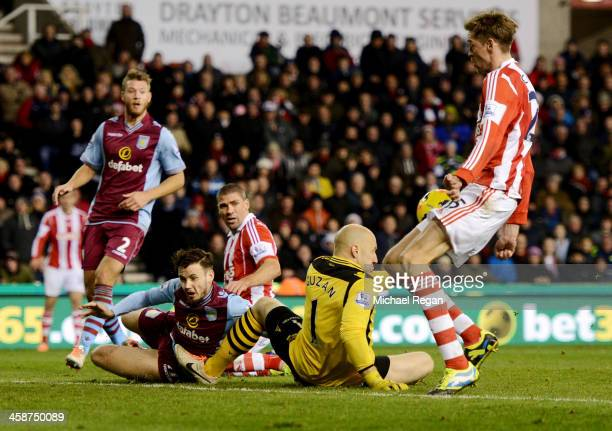 Peter Crouch of Stoke City bundles the the ball past Brad Guzan of Aston Villa as he scores their second goal during the Barclays Premier League...