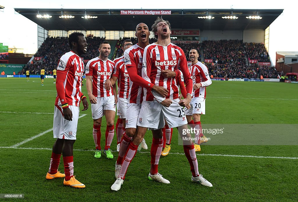 Peter Crouch of Stoke City celebrates scoring the opening goal with his team-mates during the Barclays Premier League match between Stoke City and Arsenal at the Britannia Stadium on December 6, 2014 in Stoke on Trent, England.