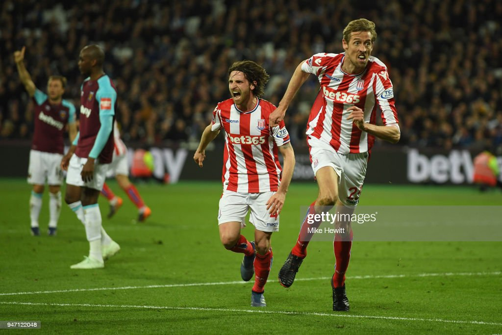 Peter Crouch of Stoke City celebrates with team mate Joe Allen of Stoke City after scoring his sides first goal during the Premier League match between West Ham United and Stoke City at London Stadium on April 16, 2018 in London, England.
