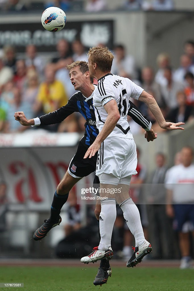 Peter Crouch (L) of Stoke City challenged by Garry Monk (R) of Swansea City during the Barclays Premier League match between Swansea City and Stoke City at the Liberty Stadium on October 2, 2011 in Swansea, Wales.