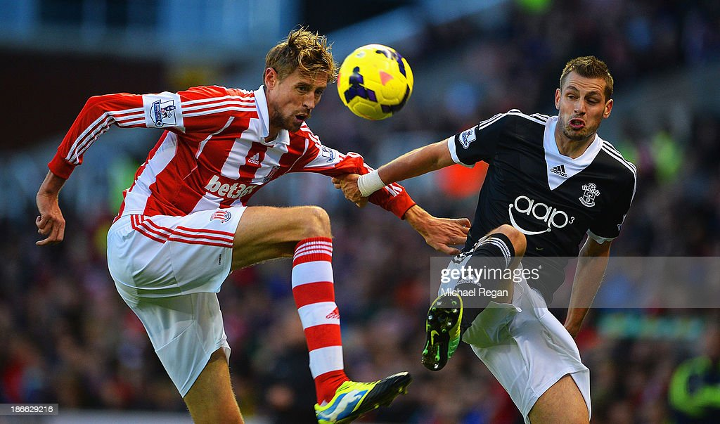 Peter Crouch of Stoke City challenges for the ball with Morgan Schneiderlin of Southampton during the Barclays Premier League match between Stoke City and Southampton at Britannia Stadium on November 2, 2013 in Stoke on Trent, England.