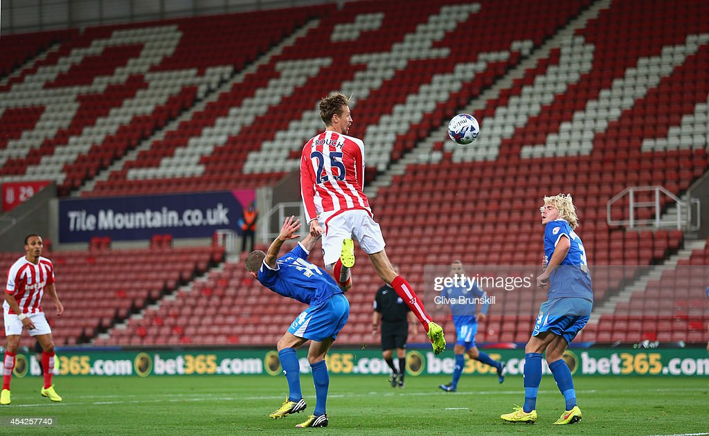 Peter Crouch of Stoke City heads at goal in front of a completely empty stand during the Capital One Cup Second Round match between Stoke City and Portsmouth at Britannia Stadium on August 27, 2014 in Stoke on Trent, England.