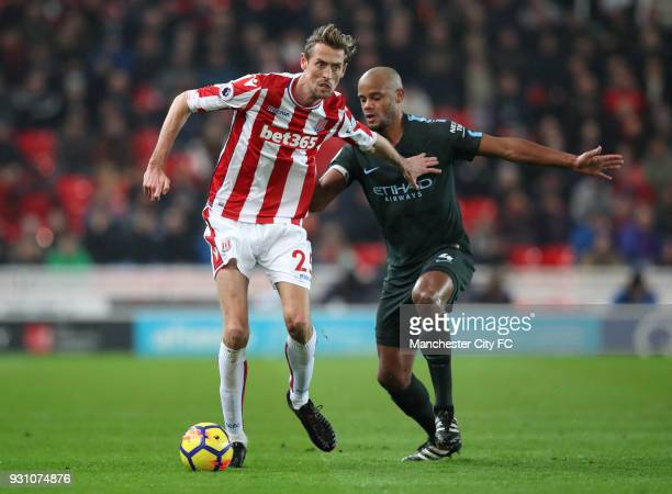 Peter Crouch of Stoke City holds off Vincent Kompany of Manchester City during the Premier League match between Stoke City and Manchester City at...