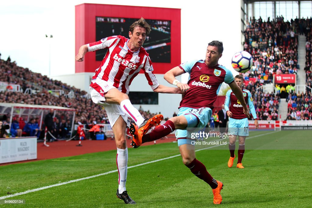 Peter Crouch of Stoke City in action with Stephen Ward of Burnley during the Premier League match between Stoke City and Burnley at Bet365 Stadium on April 22, 2018 in Stoke on Trent, England.