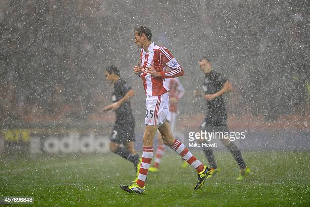 Peter Crouch of Stoke City runs off as heavy rain falls and play is halted during the Capital One Cup Quarter Final match between Stoke City and...