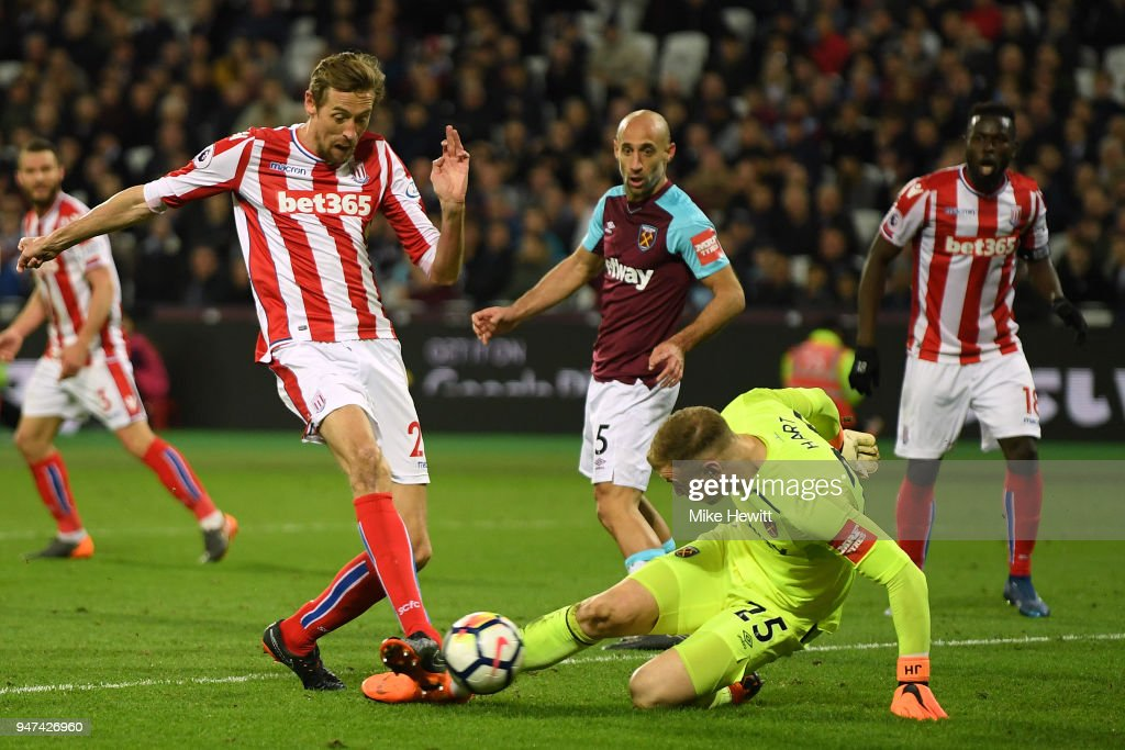 Peter Crouch of Stoke City scores despite the efforts of Joe Hart of West Ham United during the Premier League match between West Ham United and Stoke City at London Stadium on April 16, 2018 in London, England.
