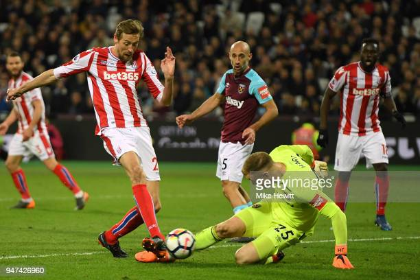 Peter Crouch of Stoke City scores despite the efforts of Joe Hart of West Ham United during the Premier League match between West Ham United and...
