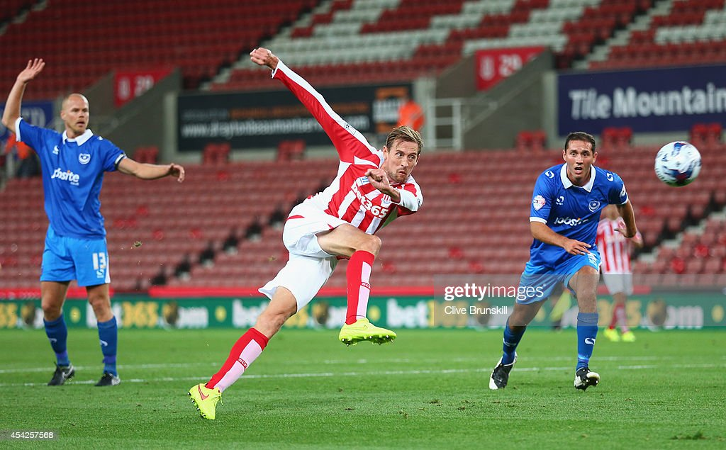Peter Crouch of Stoke City shoots at goal watched by the Portsmouth defence during the Capital One Cup Second Round match between Stoke City and Portsmouth at Britannia Stadium on August 27, 2014 in Stoke on Trent, England.