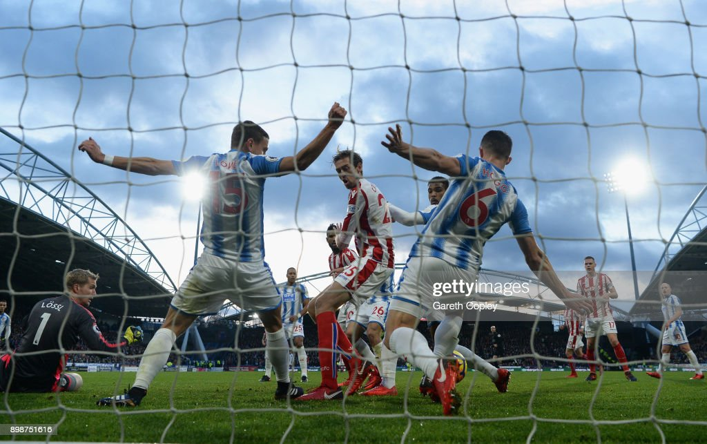 Peter Crouch of Stoke City shoots but has the ball played of the line by Chris Lowe of Huddersfield Town and Jonathan Hogg of Huddersfield Town during the Premier League match between Huddersfield Town and Stoke City at John Smith's Stadium on December 26, 2017 in Huddersfield, England.