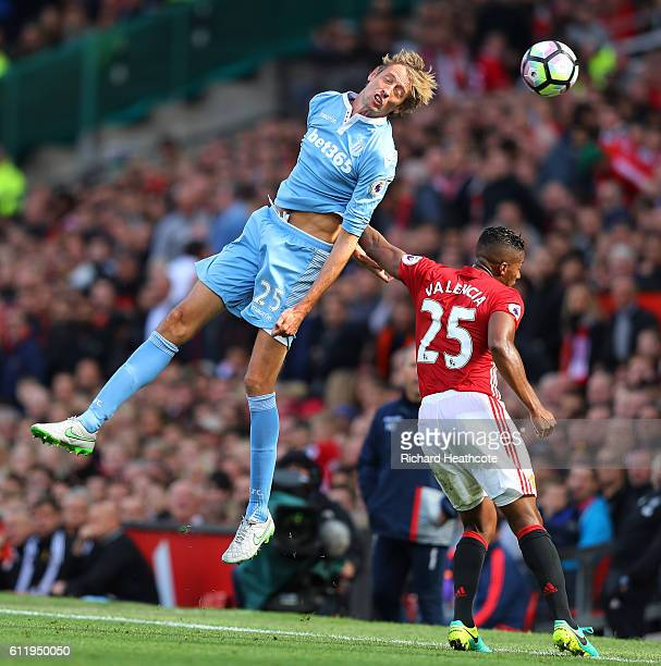 Peter Crouch of Stoke City wins a header over Antonio Valencia of Manchester United during the Premier League match between Manchester United and...