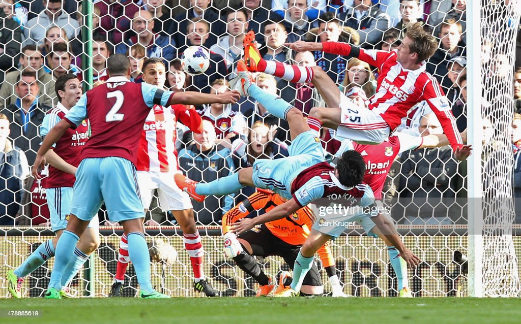 Peter Crouch of Stoke City's (25) shot deflects in to the goal off of Peter Odemwingie of Stoke City for their first as James Tomkins of West Ham United (5) challenges during the Barclays Premier League match between Stoke City and West Ham United at Britannia Stadium on March 15, 2014 in Stoke on Trent, England.