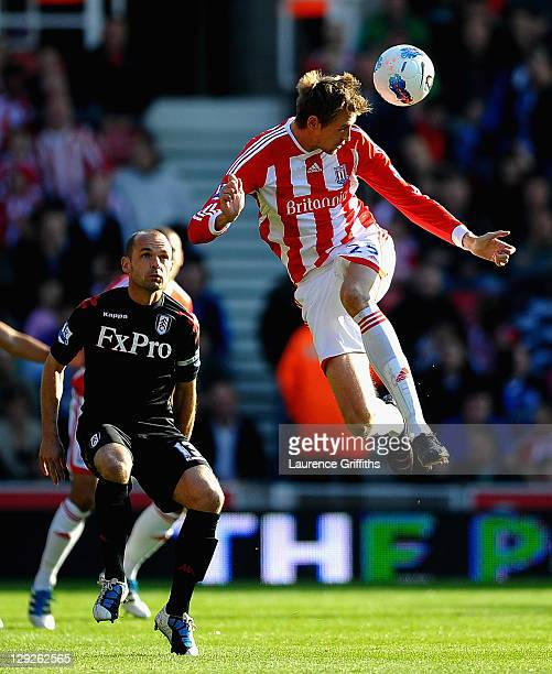 Peter Crouch of Stoke rises for a header in front of Danny Murphy of Fulham during the Barclays Premier League match between Stoke City and Fulham at...