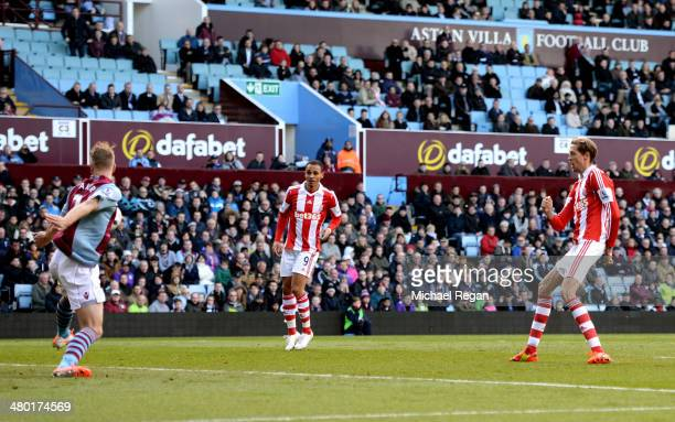 Peter Crouch of Stoke shoots past Nathan Baker of Aston Villa to score his team's second goal during the Barclays Premier League match between Aston...