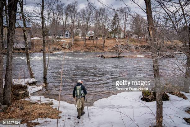 Peter Crowell of Brunswick walks through snow to get to the Nezinscot River in Turner as he took part in the first day of open water fishing on...
