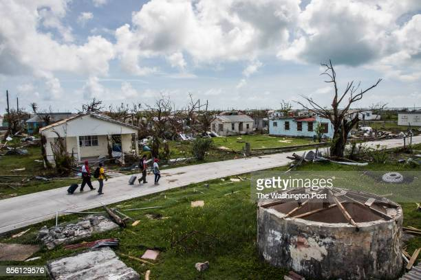 Peter Cuffy and his wife Jenita Cuffy walk behind a Red Cross crew as they look at the damages on the island of Barbuda in the aftermath of Hurricane...