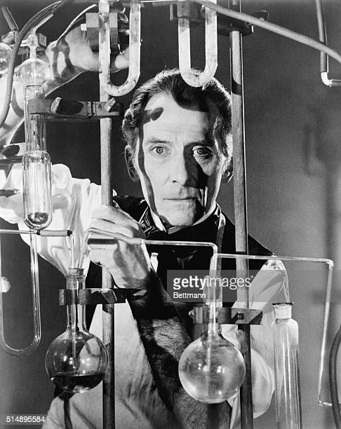 Peter Cushing poses as a scientist in a laboratory behind a rack of flasks and glass tubing Undated movie still