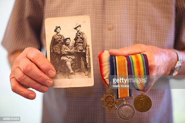 Peter Dowsett son of ANZAC veteran Victor Sydney Dowsett poses with a wartime photograph of father and his uncle Robert William Dowsett while holding...