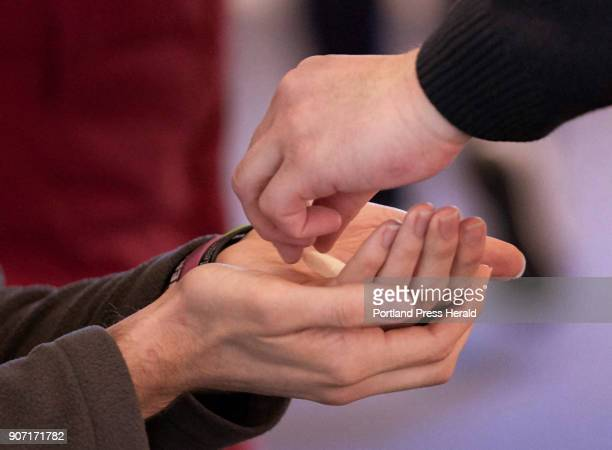 Peter Doyle right an eucharistic minister at the Cathedral of the Immaculate Conception in Portland places the host into the hands of a man while...