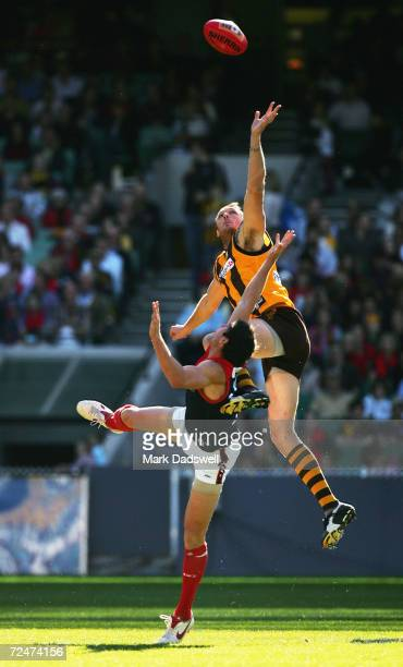 Peter Everitt for the Hawks leaps over Jeff White for the Demons during the AFL Round 8 match between the Hawthorn Hawks and the Melbourne Demons at...