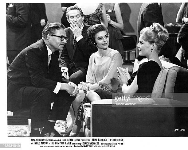 Peter Finch Anne Bancroft James Mason and Janine Gray sitting together at a cocktail lounge in a scene from the film 'The Pumpkin Eater' 1964