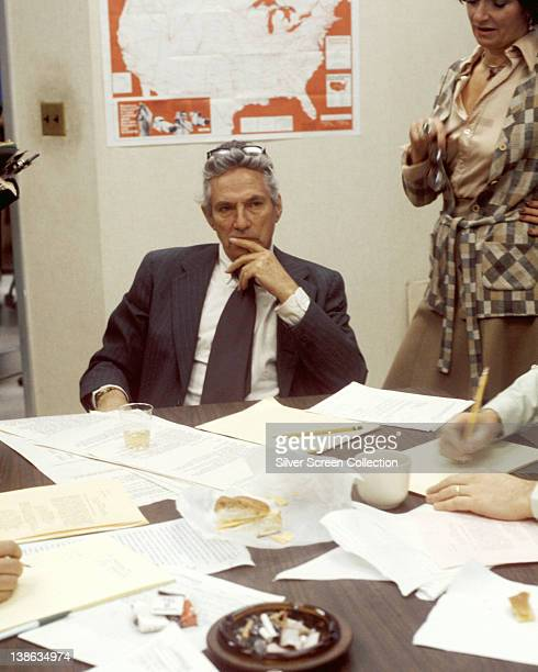 Peter Finch British actor sitting behind a desk with a pensive expression on his face in a publicity still issued for the film 'Network' 1976 The...