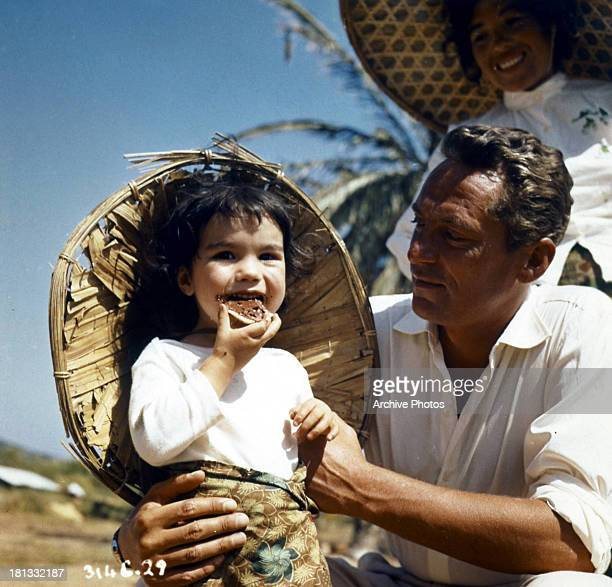 Peter Finch carries a toddler in a scene from the film 'Windom's Way' 1957