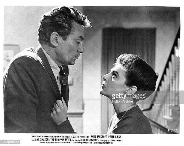 Peter Finch is taking Anne Bancroft very seriously as she grabs his lapel and stares him in the eyes with anger in a scene from the film 'The Pumpkin...