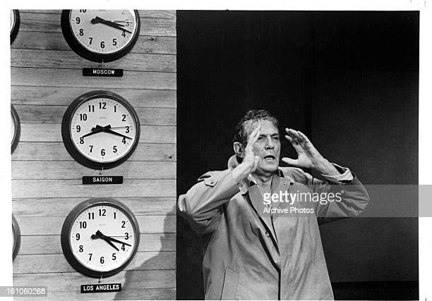 Peter Finch on set in front of wall of clocks in a scene from the film 'Network' 1976