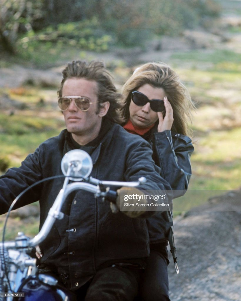 Peter Fonda, US actor, and Nancy Sinatra, US actress and singer, riding a motorcycle, with both wearing sunglasses in a publicity still issued for the film, 'The Wild Angels', USA, 1966. The Hells Angels drama, directed by Roger Corman, starred Fonda as 'Heavenly Blues', and Sinatra as 'Mike'.