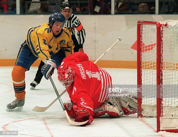 Peter Forsberg of Team Sweden slides the puck past goalie Corey Hirsch of Team Canada to score the winning goal during the shoot-out of the ice...