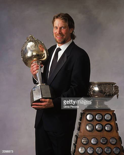 Peter Forsberg of the Colorado Avalanche poses with the Art Ross Trophy and Hart Memorial Trophy during the 200203 NHL Awards at the Convention...