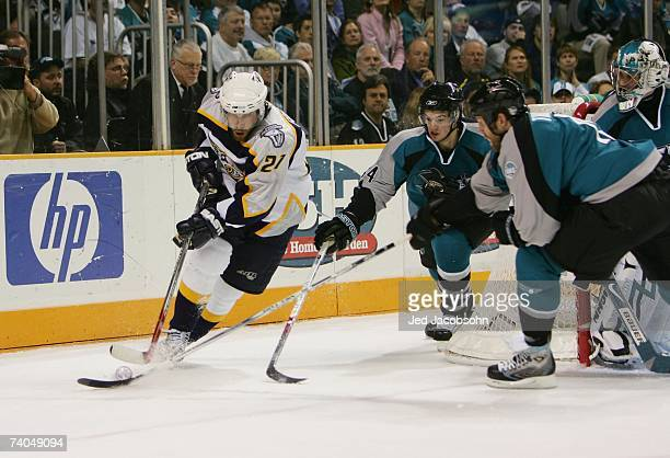 Peter Forsberg of the Nashville Predators is pressured by Marc-Edouard Vlasic of the San Jose Sharks as he skates with the puck in Game 4 of the...