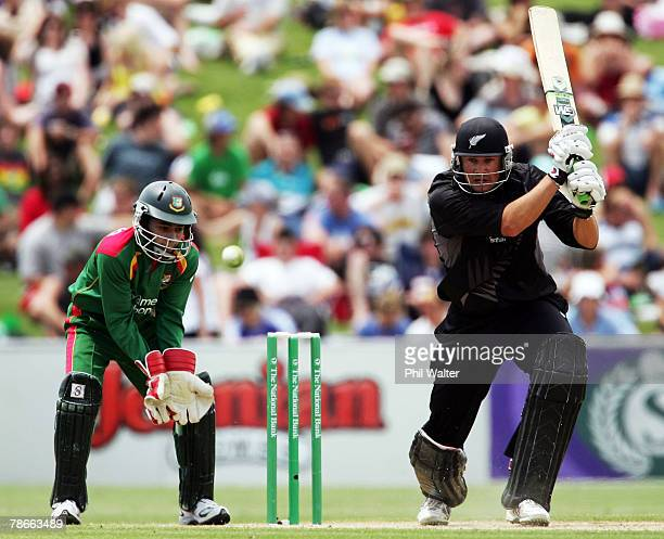 Peter Fulton of New Zealand plays a shot watched by Mushfiqur Rahim of Bangladesh during the second one day international match between New Zealand...