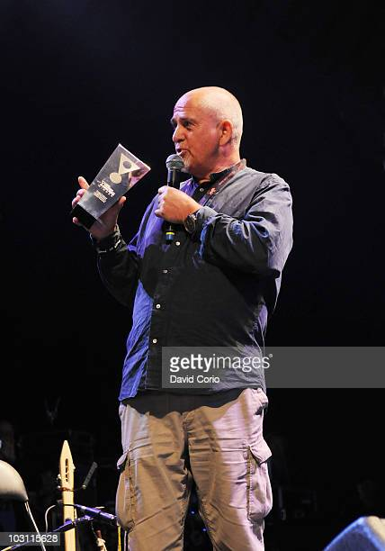 Peter Gabriel appears on stage with a Songlines Music Award for Justin Adams and Juldeh Camara during the second day of Womad Festival at Charlton...