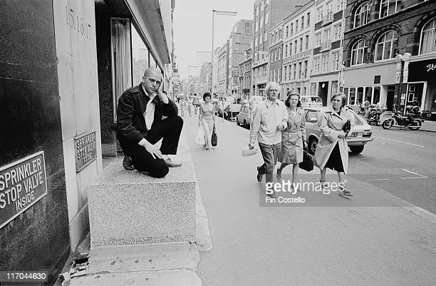 Peter Gabriel British singersongwriter and musician kneeling shaven head with his head resting on his hand as groups of people pass by in London...