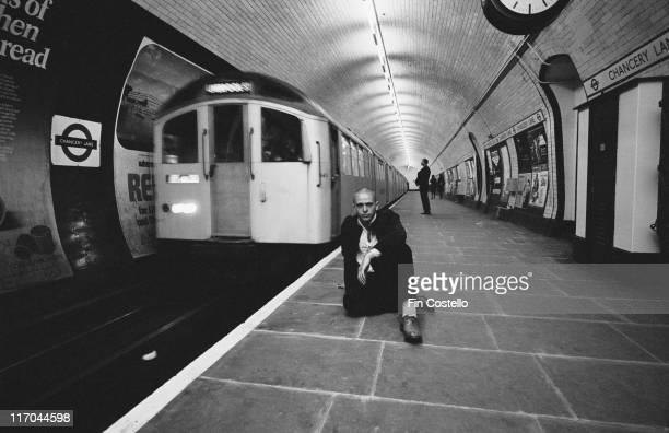 Peter Gabriel British singersongwriter and musician poses shaven head sitting on a platform at Chancery Lane underground station in London England...