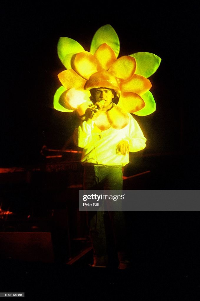 Peter Gabriel on stage wearing a flower costume while performing
