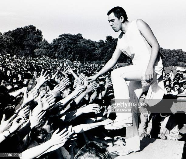 Peter Gabriel reaches out from the stage to touch the hands of fans reaching up from the audience while performing on stage as support to The...