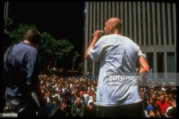 Peter Garrett lead singer for Australian rock group Midnight Oil singing outside Exxon bldg in protest against previous year's oil spill in Alaska